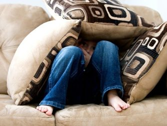 little boy hiding in pillows afraid